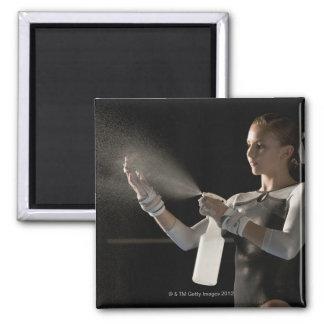 Gymnast spraying water on hands magnet