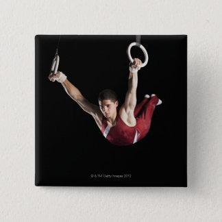 Gymnast swinging from rings button