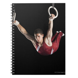 Gymnast swinging from rings note books