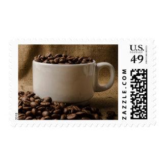 Habas del amante del café en un sello de la taza