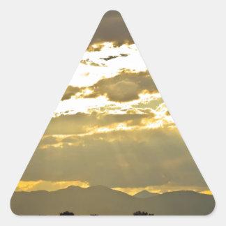 Haces de oro de la luz del sol que brillan abajo pegatina triangular