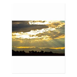 Haces de oro de la luz del sol que brillan abajo postales