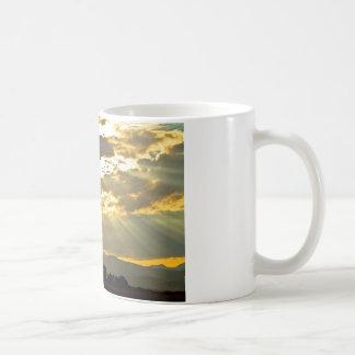 Haces de oro de la luz del sol que brillan abajo taza de café