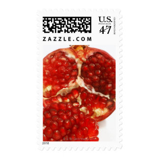 Half a ripe pomegranate cut to expose the juicy postage
