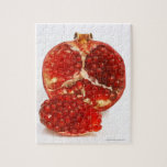 Half a ripe pomegranate cut to expose the juicy jigsaw puzzle