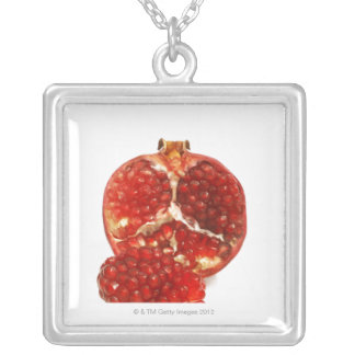 Half a ripe pomegranate cut to expose the juicy silver plated necklace