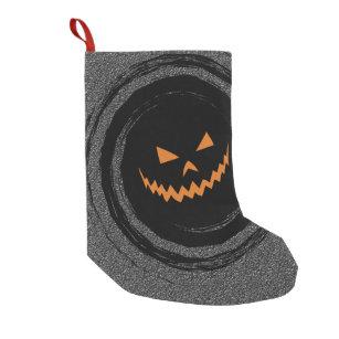 halloween glowing jack olantern in a black swirl small christmas stocking