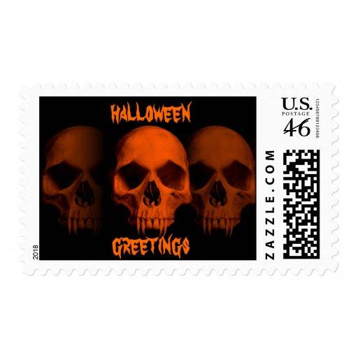 Halloween horror fanged skulls in black and orange postage stamp