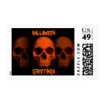 Halloween horror fanged skulls in black and orange postage