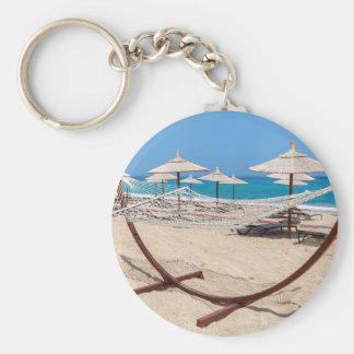 Hamaca con los parasoles de playa en la costa llavero redondo tipo pin