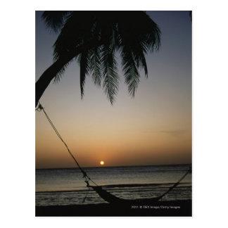 Hamaca vacía de Silhuetted en la puesta del sol Tarjetas Postales