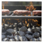Hamburgers cooking on grill large square tile