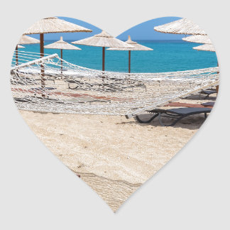 Hammock with beach umbrellas at coast heart sticker