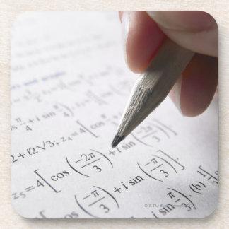 Hand doing math homework coaster
