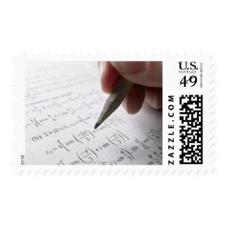 Hand doing math homework postage stamps