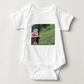 Hand holding a smart phone and nature background baby bodysuit