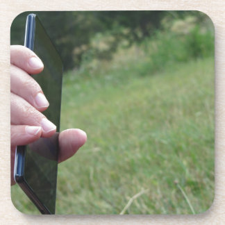 Hand holding a smart phone and nature background beverage coaster
