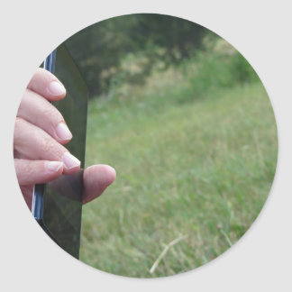 Hand holding a smart phone and nature background classic round sticker