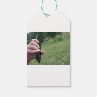 Hand holding a smart phone and nature background gift tags