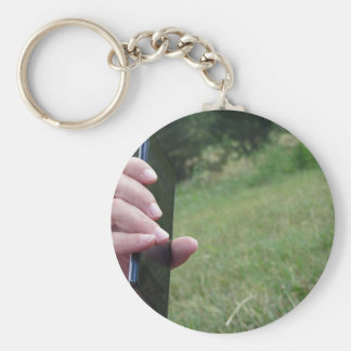 Hand holding a smart phone and nature background keychain