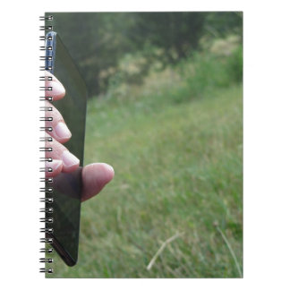 Hand holding a smart phone and nature background notebook