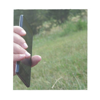 Hand holding a smart phone and nature background notepad