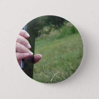 Hand holding a smart phone and nature background pinback button