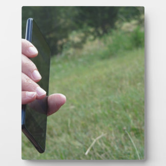 Hand holding a smart phone and nature background plaque