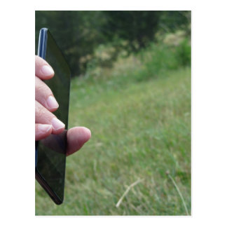 Hand holding a smart phone and nature background postcard
