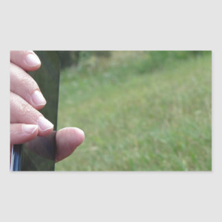 Hand holding a smart phone and nature background rectangular sticker