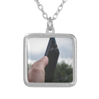 Hand holding a smart phone and nature background silver plated necklace
