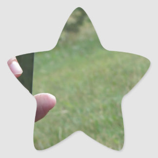 Hand holding a smart phone and nature background star sticker