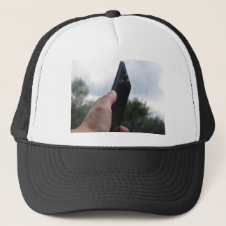Hand holding a smart phone and nature background trucker hat
