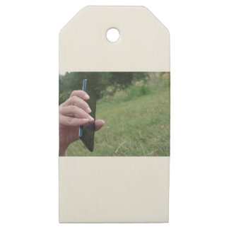 Hand holding a smart phone and nature background wooden gift tags