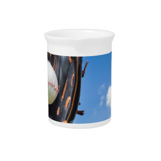 Hand holding baseball in glove with blue sky beverage pitcher