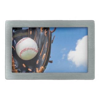 Hand holding baseball in glove with blue sky rectangular belt buckle
