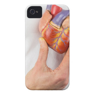 Hand holding model heart on chest iPhone 4 Case-Mate case