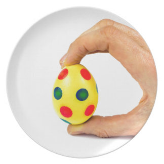Hand holding painted yellow easter egg with dots dinner plate