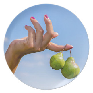 Hand holding two hanging green pears in blue sky melamine plate