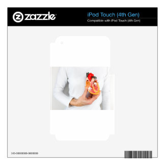 Hand holds human heart model at body decal for iPod touch 4G