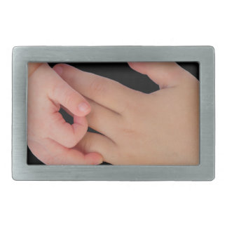 Hand of baby touching hand of child belt buckle