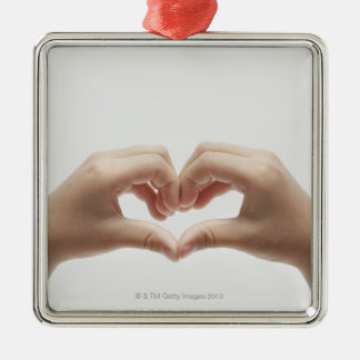 Hand of child who made shape of heart metal ornament