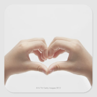 Hand of child who made shape of heart square stickers