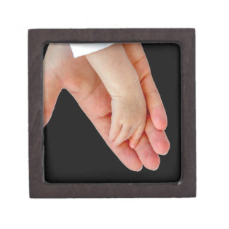 Hand of mother with arm of baby on black jewelry box