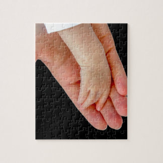 Hand of mother with arm of baby on black jigsaw puzzle