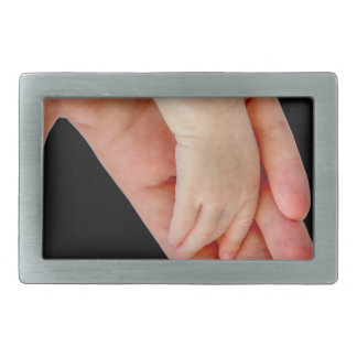 Hand of mother with arm of baby on black rectangular belt buckle
