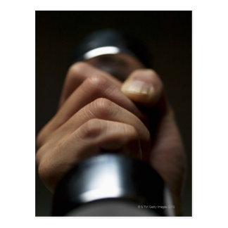 Hand of person lifting weights postcard