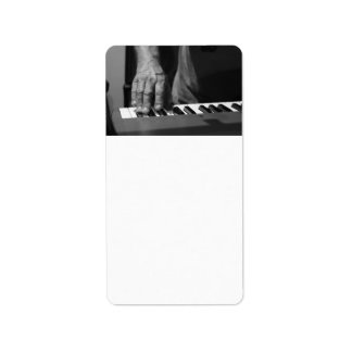 hand playing keyboard bw male music labels