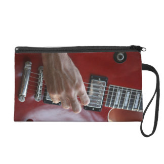 Hand playing red electric guitar near pickup wristlet clutch