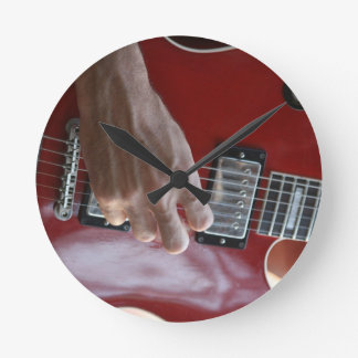 Hand playing red electric guitar near pickup clock